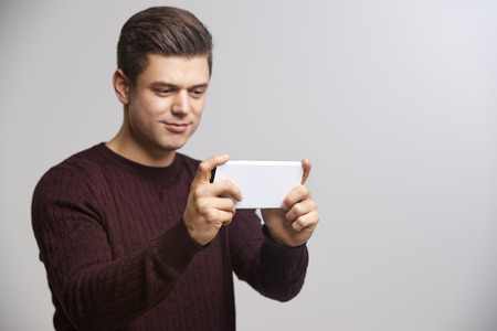 Young white man taking a selfie with his smartphone