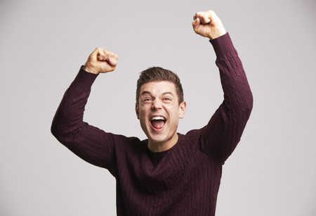 Portrait of a celebrating young white man punching the air