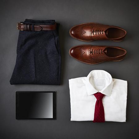 tiro plano de ropa de negocios masculino y tableta digital