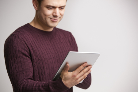 Smiling young white man using a tablet computer Stok Fotoğraf