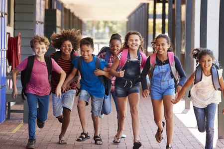 School kids running in elementary school hallway, front view