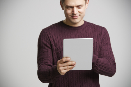 Smiling young white man holding a tablet computer
