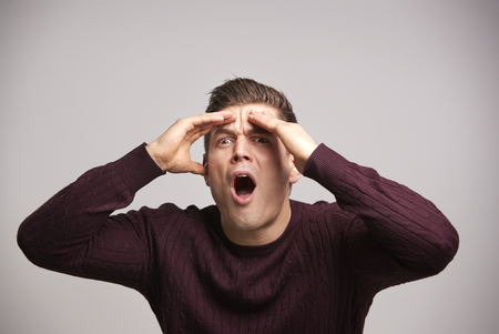 Shocked young white man with hands by his head in disbelief