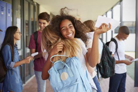Zwei Mädchen, die Prüfung feiern, resultiert in Schulkorridor Standard-Bild - 85459046