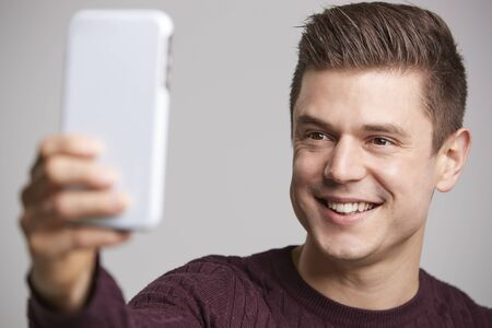 Close up of a young man taking a selfie with his smartphone