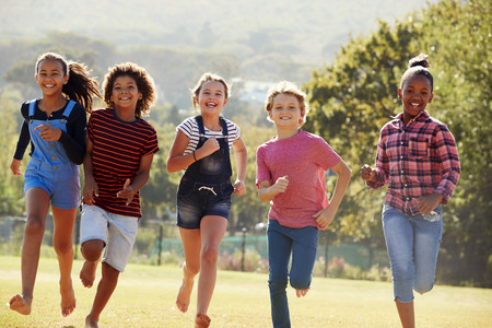 Six pre-teen friends running in a park, front view, close up Stock Photo - 85459838