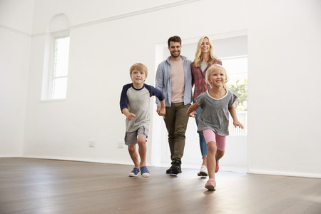 Excited Family Explore New Home On Moving Day Standard-Bild