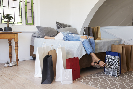 Woman Back From Shopping Trip Surrounded By Bags Lies On Bed Reklamní fotografie - 85653609