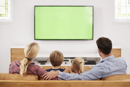 Vista trasera de la familia sentada en el sofá en el salón viendo televisión Foto de archivo - 85653664