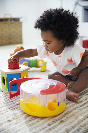 Cute Baby Girl Having Fun In Playroom With Toys