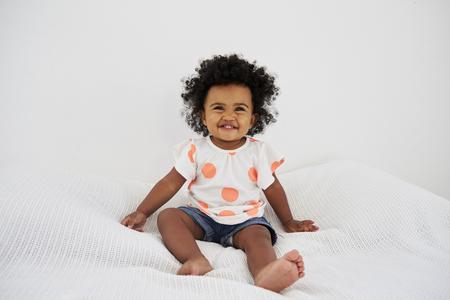 침대에 앉아 웃는 아기 소녀의 초상화