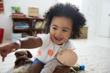 Gelukkig babymeisje spelen met pop in speelkamer