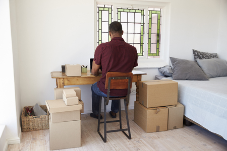 Rear View Of Man Running Business From Home Dispatching Goods