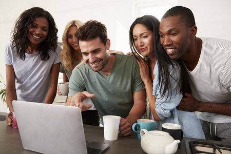 Friends Looking At Laptop And Drinking Coffee In Modern Kitchen