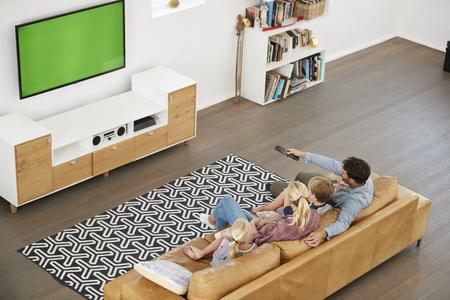 Hoge hoekmening van familiezitting op bank in zitkamer die op TV let Stockfoto