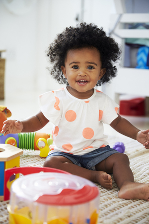 Portrait Of Baby Girl Having Fun In Playroom With Toys Stock Photo