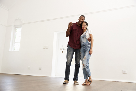Portrait Of Excited Young Couple Moving Into New Home Together