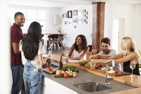 Friends Prepare And Serve Food For Dinner Party At Home Together Stock Photo