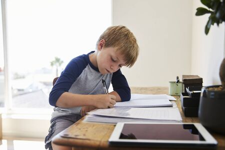 Boy Sits At Desk In Bedroom With Digital Tablet Doing Homework Stock Photo
