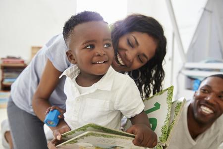 Famiglia con i bambini che leggono insieme il libro in stanza dei giochi Archivio Fotografico
