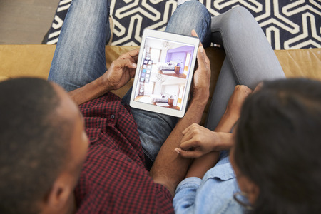 Couple Sitting On Sofa Looking At Home Improvement App Banque d'images