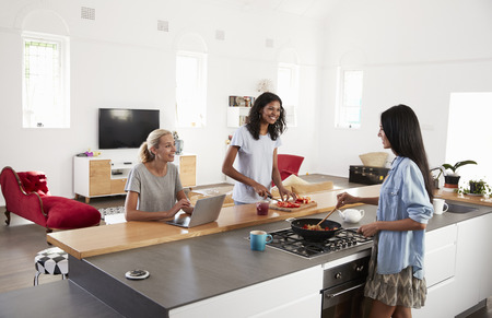 Three Female Friends Preparing Meal Together In Modern Kitchen Banque d'images