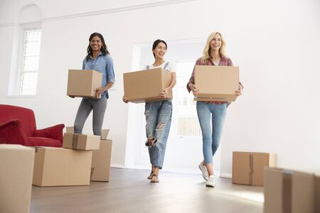 Three Female Friends Carrying Boxes Into New Home On Moving Day