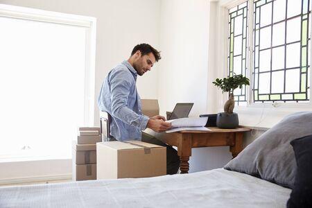 집에서 사업을 실행하는 침실에서 사람은 집으로 물건을 파견한다.