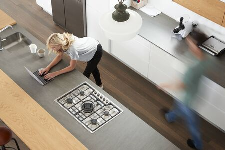 Overhead View Of Busy Couple In Modern Kitchen