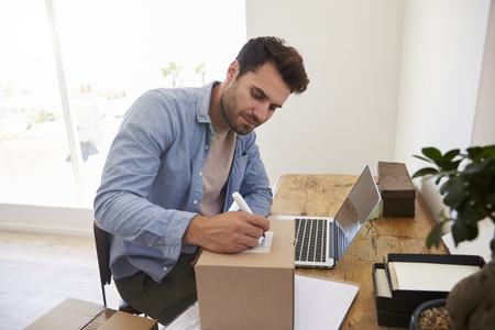Man In Bedroom Running Business From Home Labeling Goods Banque d'images