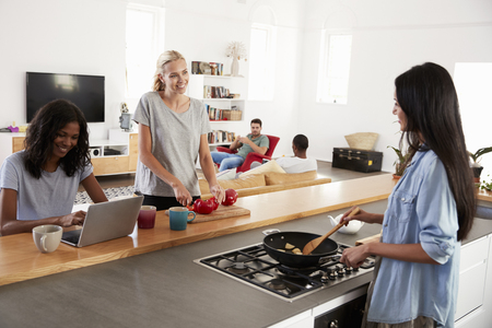 Friends Preparing Meal Together In Modern Kitchen