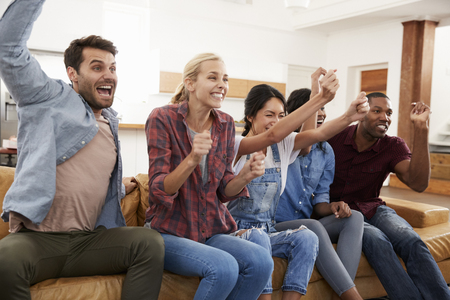 Group Of Young Friends Watching Sports On Television And Cheering Stock Photo