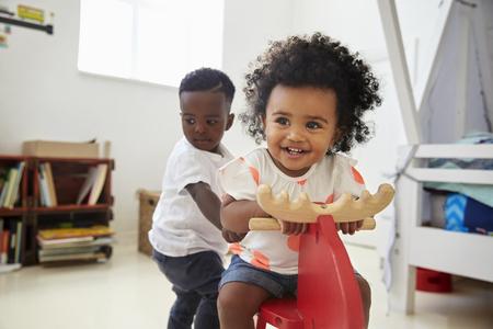 プレイルームでおもちゃに乗って座っている2人の子供たち 写真素材