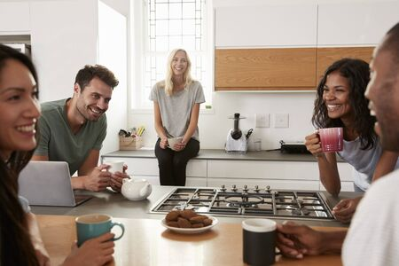 Friends Talking And Drinking Coffee In Modern Kitchen
