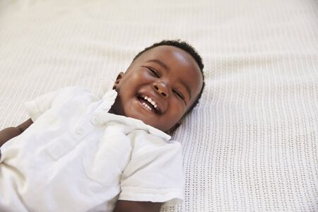 Overhead Shot Of Smiling Young Boy Lying On Bed