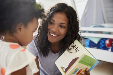 お母さんと赤ちゃんの娘が一緒にプレイルームで本を読む