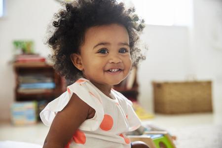 プレイルームでおもちゃで遊んで幸せな女の赤ちゃん
