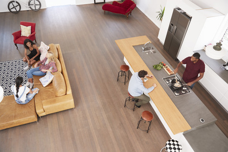 Overhead Shot Of Friends Cooking Meal And Relaxing Together