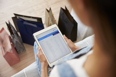 Woman With Shopping Bags Checks Bank Statement On Digital Tablet