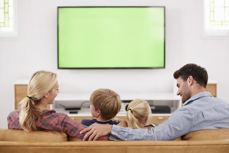 텔레비전을보고 라운지에서 소파에 앉아 가족의 후면보기 스톡 콘텐츠