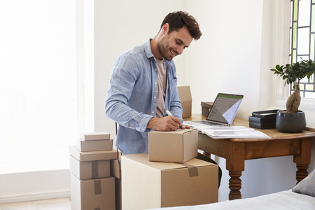 Man In Bedroom Running Business From Home Labeling Goods 스톡 콘텐츠