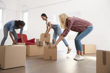 이사의 날에 새 집에 상자를 들고 세 여자 친구