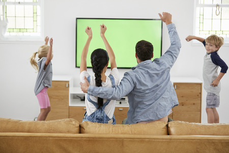 Family Watching Sports On Television And Cheering Stock Photo