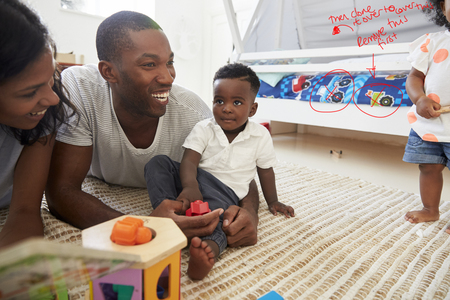 Family With Baby Son Reading Book In Playroom Together