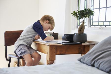 Boy Sits At Desk In Bedroom With Digital Tablet Doing Homework Reklamní fotografie
