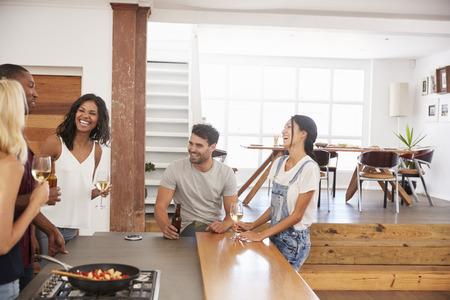 Friends Prepare And Serve Food For Dinner Party At Home Together Reklamní fotografie