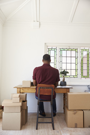 addressing: Man In Bedroom Running Business From Home Labeling Goods Stock Photo