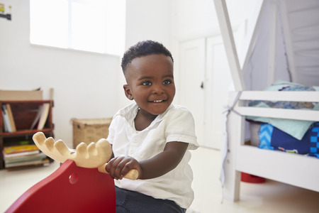 Young Boy Sitting On Ride On Toy In Playroom