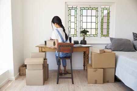 가정에서 사업을 실행하는 침실에서 여자는 상품을 파견