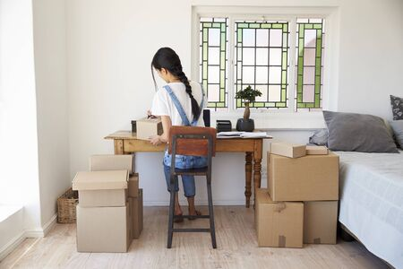 Woman In Bedroom Running Business From Home Dispatching Goods Stock Photo